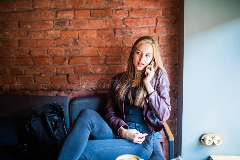 Vrolijke jonge op telefoon spreken en vrouw die terwijl het genieten van van koffie in koffie glimlachen stock afbeeldingen