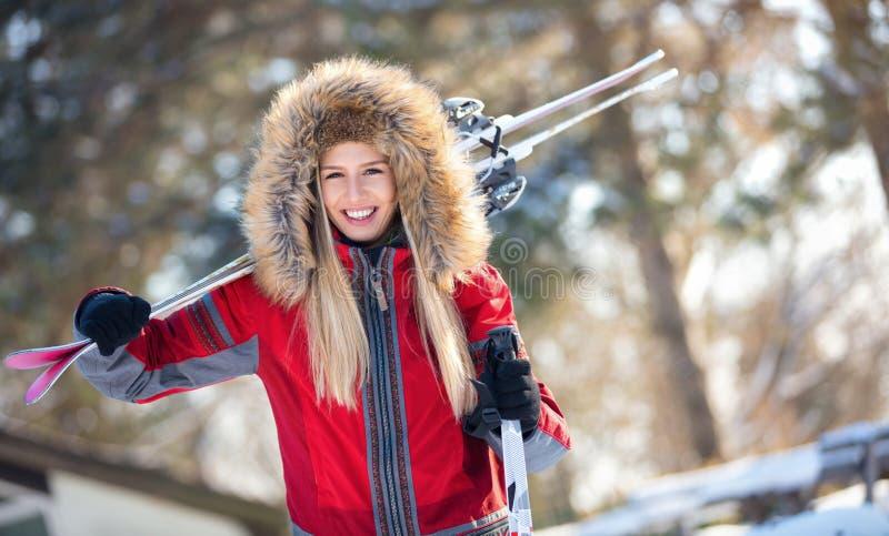 Vrolijke jonge skiër met skis en polen stock foto's