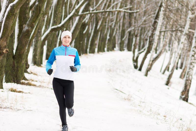 Vrolijke jonge sportvrouw bij de winter openluchtactiviteit stock afbeelding