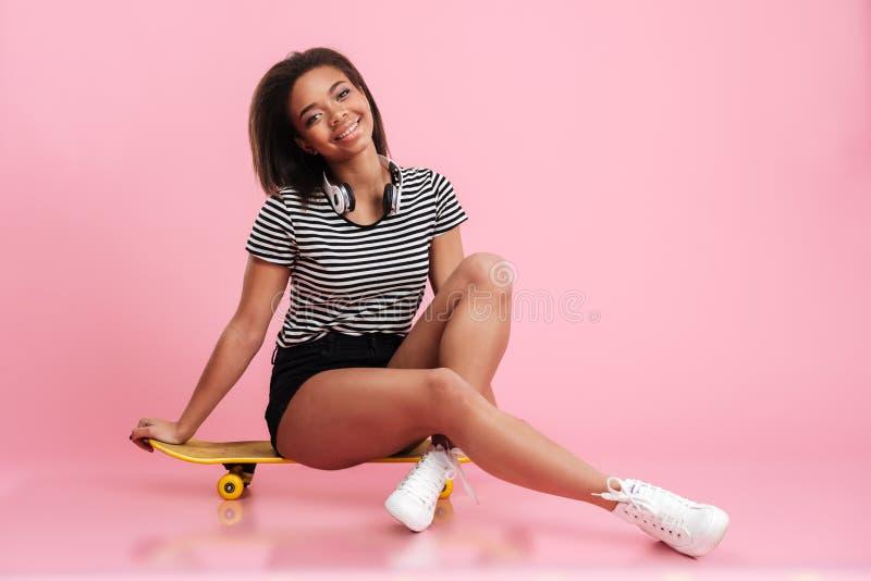Vrolijke jonge tienerzitting op een skateboard stock foto
