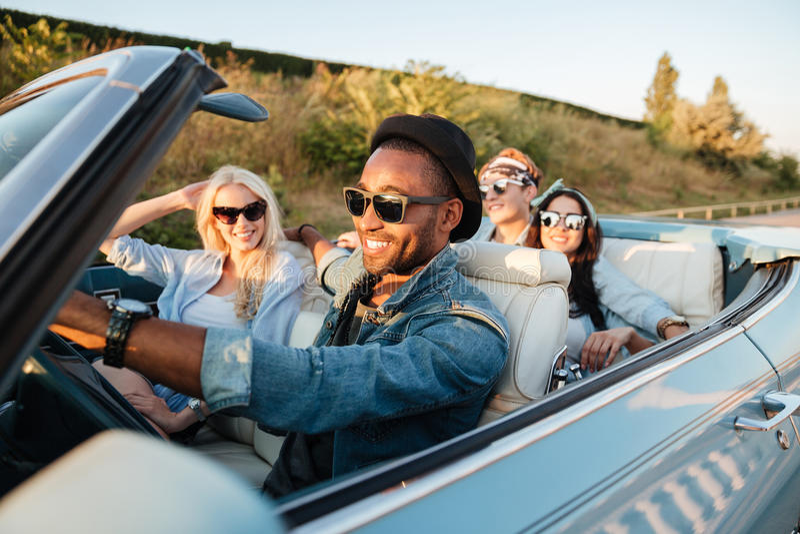 Vrolijke jonge vrienden die auto drijven en in de zomer glimlachen stock afbeelding