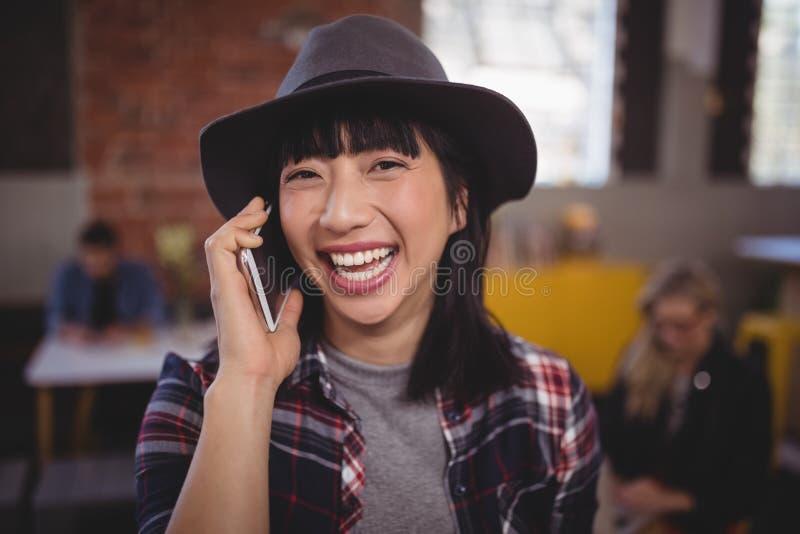 Vrolijke jonge vrouw die aan mobiele telefoon bij koffiewinkel luisteren stock foto