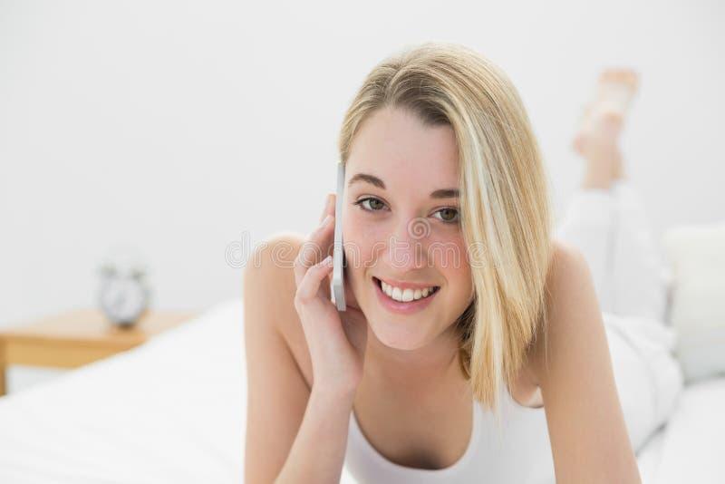 Vrolijke jonge vrouw die bij camera glimlachen terwijl het telefoneren met haar smartphone stock fotografie