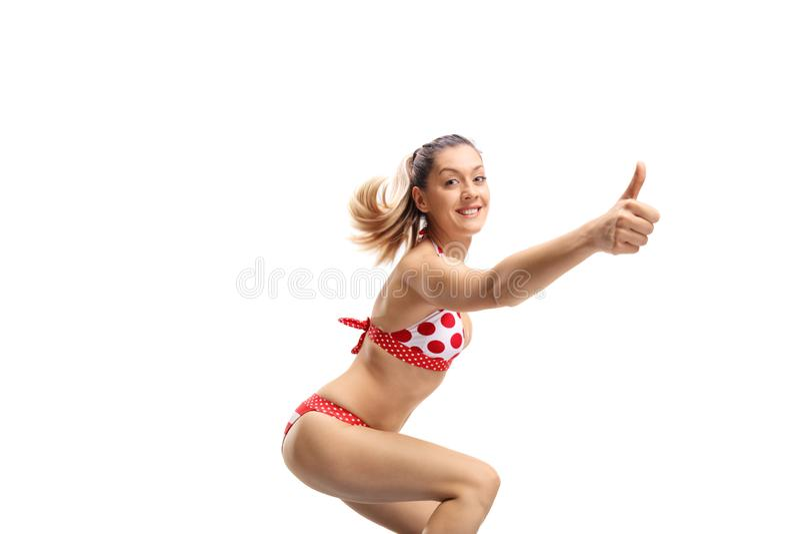 Vrolijke jonge vrouw die in bikini een duim op gebaar maken royalty-vrije stock fotografie