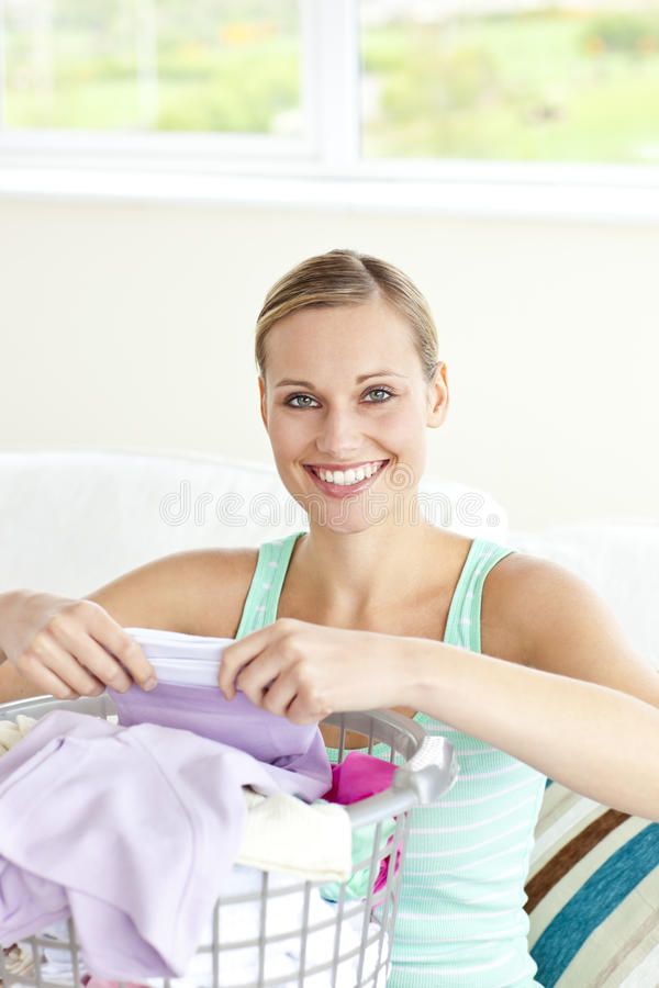 Vrolijke jonge vrouw die de wasserij doet royalty-vrije stock afbeeldingen