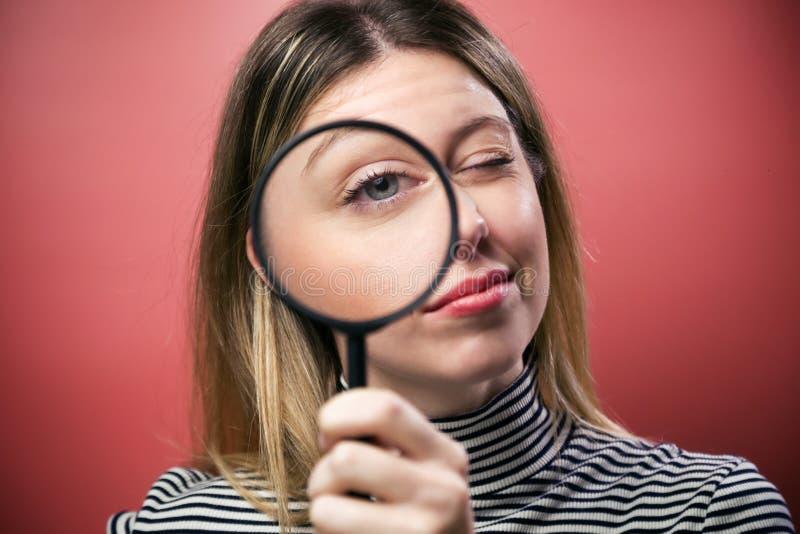 Vrolijke jonge vrouw die door vergrootglas de camera over roze achtergrond bekijken royalty-vrije stock afbeeldingen