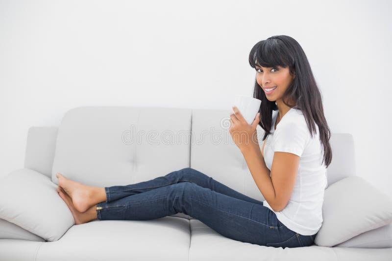 Vrolijke jonge vrouw die een kopzitting op laag houden stock afbeelding