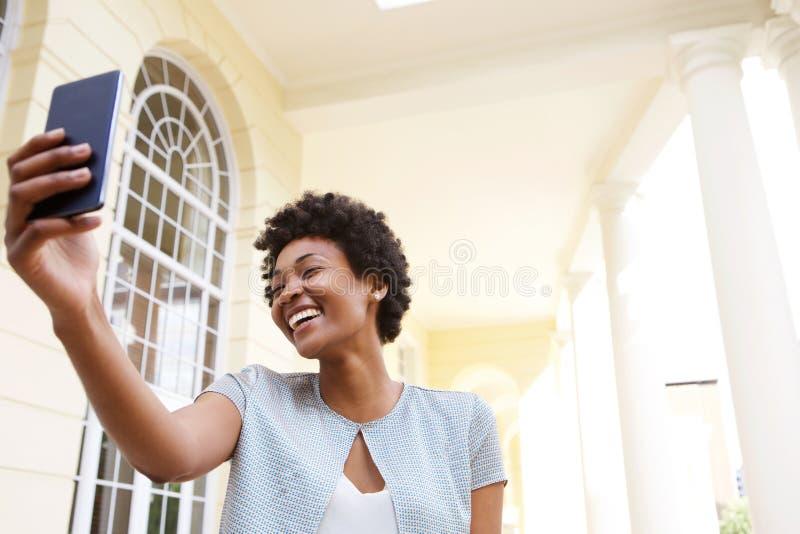 Vrolijke jonge vrouw die een selfie met haar mobiele telefoon nemen stock foto's