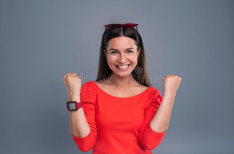 Vrolijke jonge vrouw die en vuistpompen doen grijnzen stock afbeeldingen