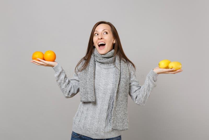 Vrolijke jonge vrouw die in grijze sweater, sjaal, citroenensinaasappelen omhoog die kijken die houden op grijze achtergrond word stock foto's