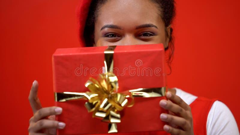 Vrolijke jonge vrouw die huidige handen, gelegenheidsgift, verjaardagsverrassing houden stock afbeeldingen