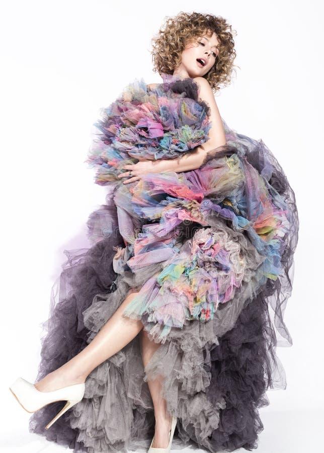 Vrolijke jonge vrouw die in kleurrijke gelaagde kleding dansen Mooi krullend haar stock afbeelding