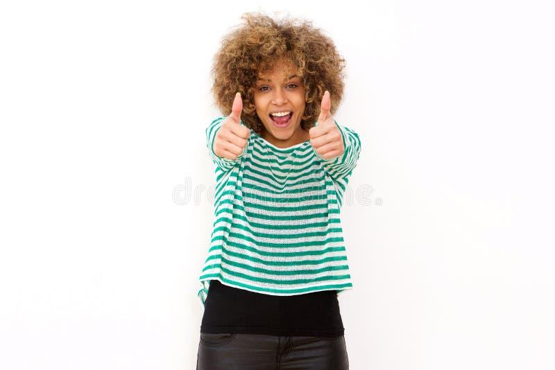 Vrolijke jonge vrouw die met duimen op handteken glimlachen royalty-vrije stock foto's