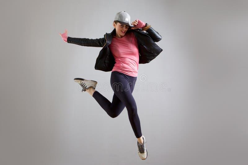 Vrolijke jonge vrouw die met hoed in de lucht tegen grijze achtergrond springen stock afbeeldingen
