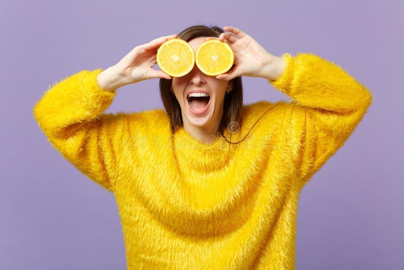 Vrolijke jonge vrouw die mond open houden, behandelend ogen met halfs van vers rijp oranje die fruit op violette pastelkleur word stock foto's