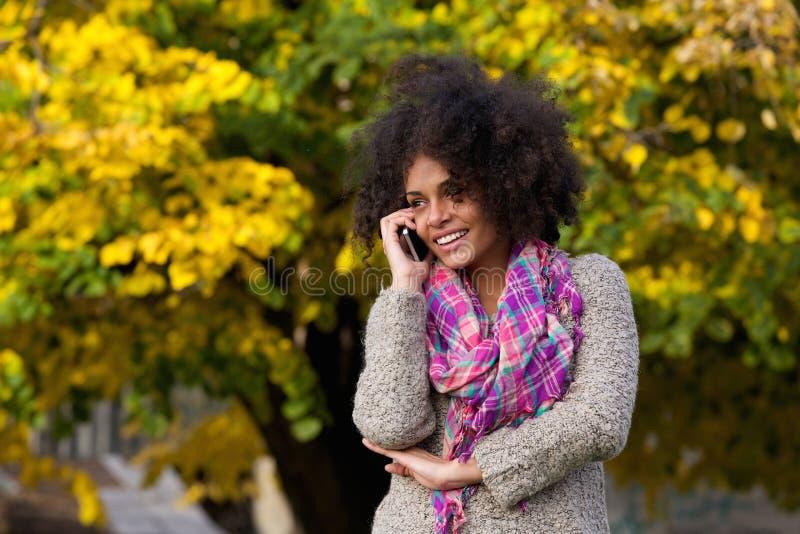 Vrolijke jonge vrouw die op celtelefoon buiten spreken stock foto's