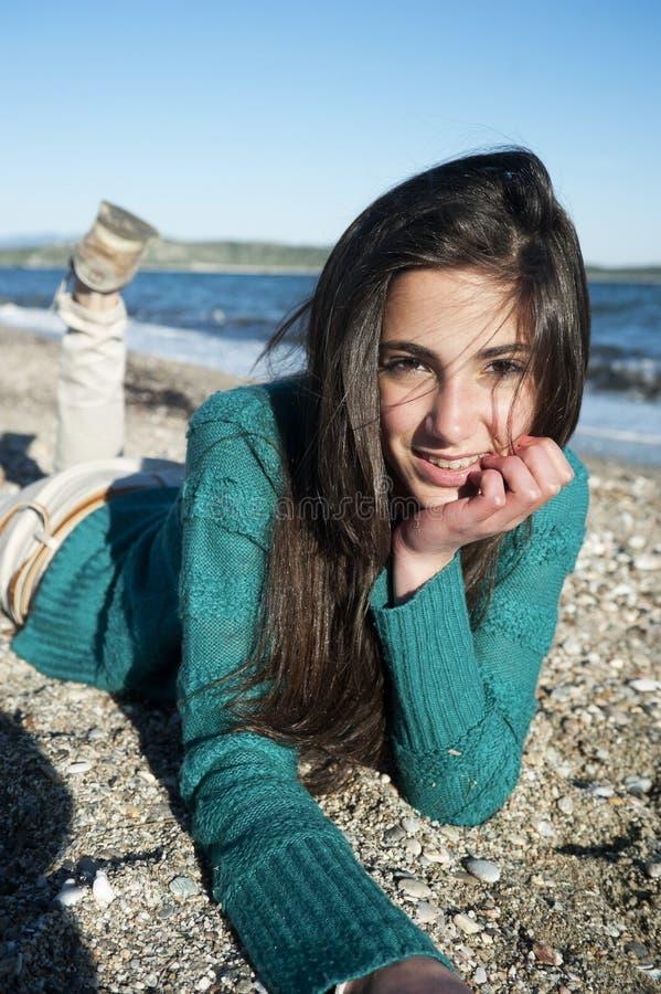 Vrolijke jonge vrouw die op het strand liggen stock afbeeldingen