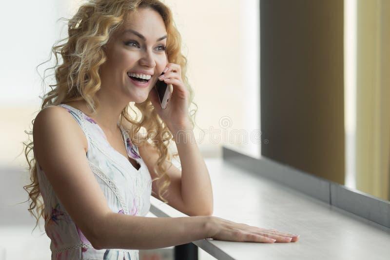 Vrolijke jonge vrouw die op mobiele telefoon en het drinken koffie bij de lijst in koffie spreken royalty-vrije stock foto's