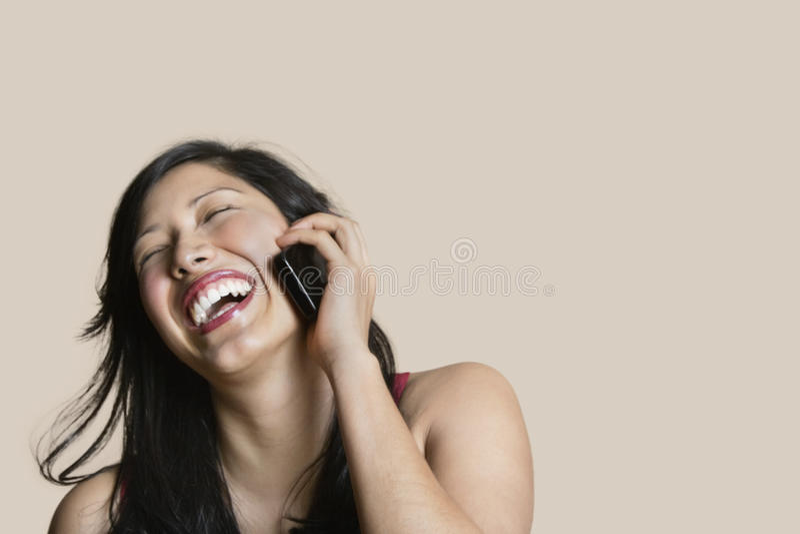 Vrolijke jonge vrouw die op mobiele telefoon over gekleurde achtergrond spreken stock afbeeldingen