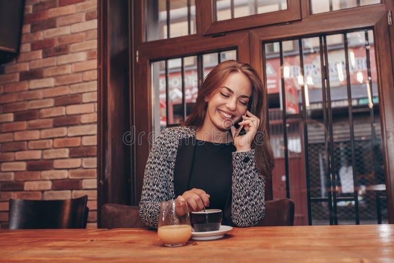 Vrolijke jonge vrouw die op telefoon in koffie spreken stock afbeelding