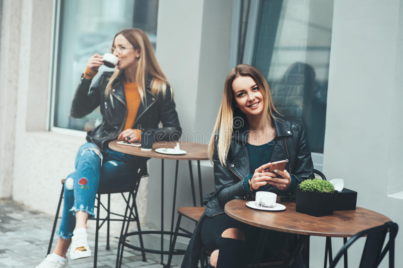 Vrolijke jonge vrouw die openlucht het drinken koffie zitten die en smartphone glimlachen houden met mooi modieus meisje op bac i stock afbeeldingen