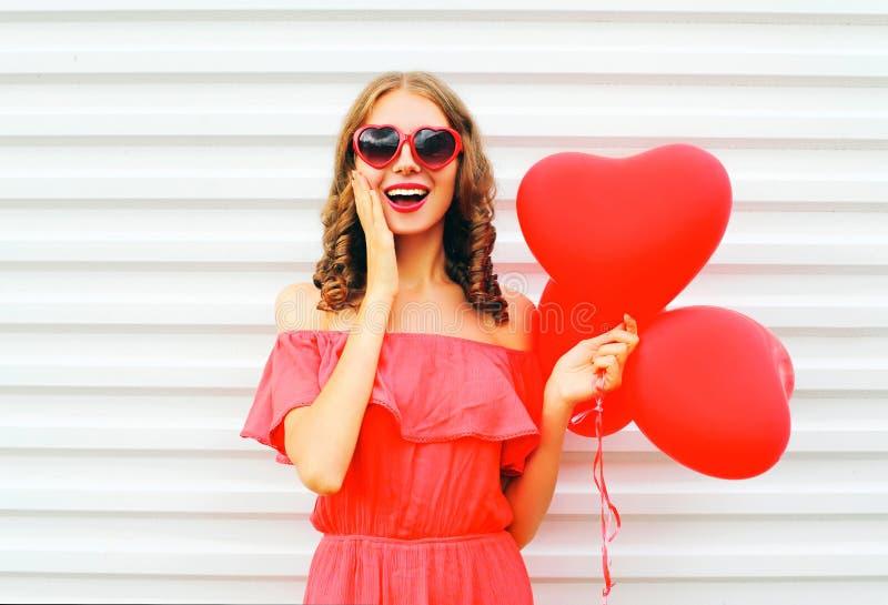 Vrolijke jonge vrouw die rode zonnebril met luchtballons hij dragen stock foto's