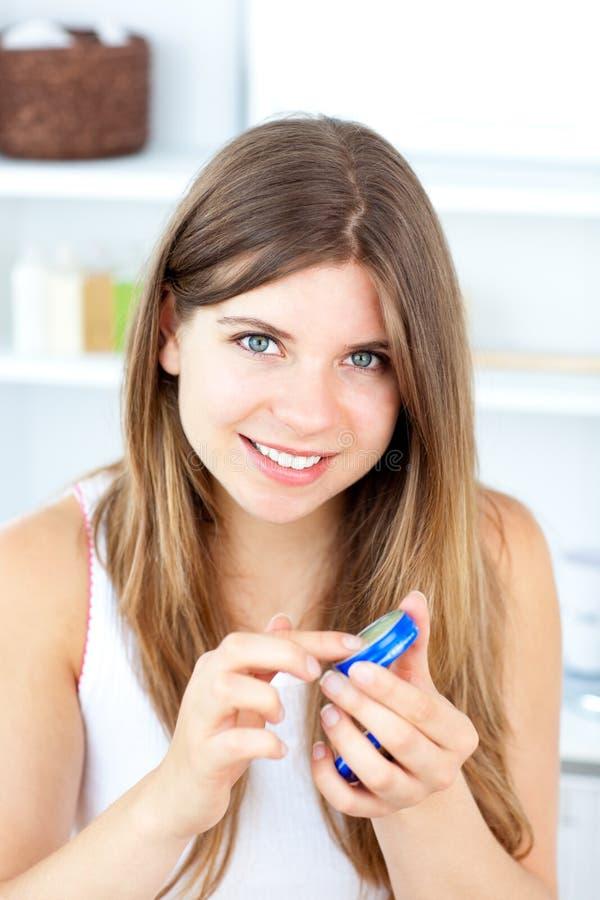 Vrolijke jonge vrouw die room voor haar lippen gebruikt stock afbeelding