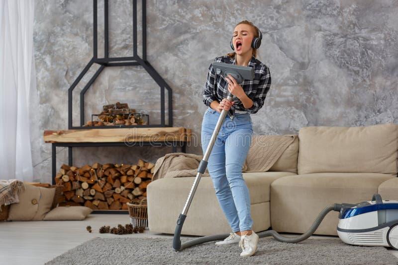 Vrolijke jonge vrouw die solo genieten van zingend met stofzuiger terwijl het schoonmaken van huis royalty-vrije stock foto