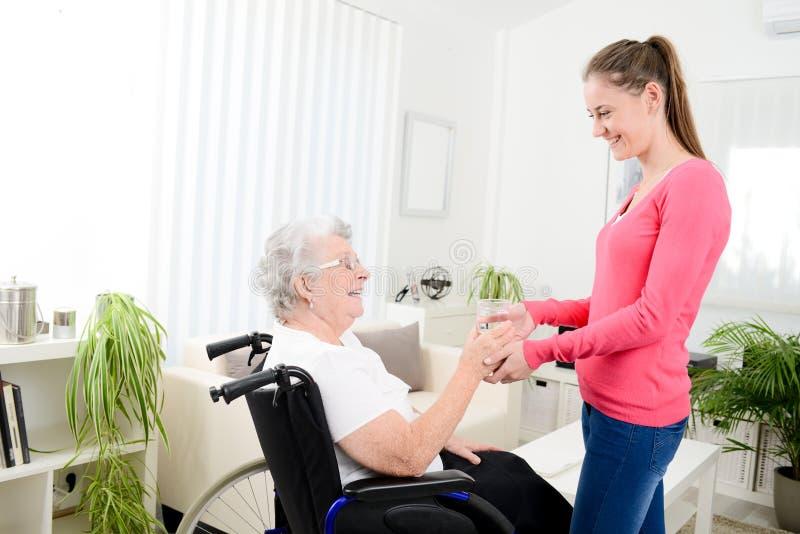Vrolijke jonge vrouw die zorg thuis van een bejaarde op een rolstoel nemen stock foto's