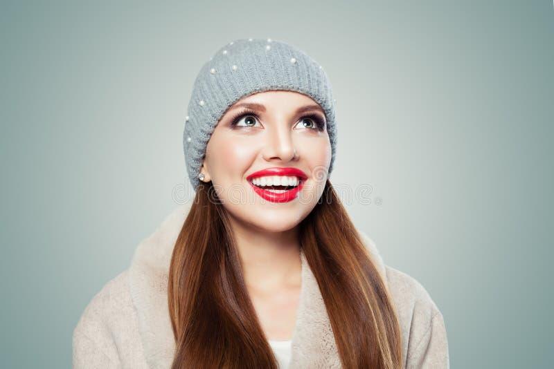 Vrolijke jonge vrouw in grijze omhooggaand en hoed die kijken glimlachen royalty-vrije stock foto's