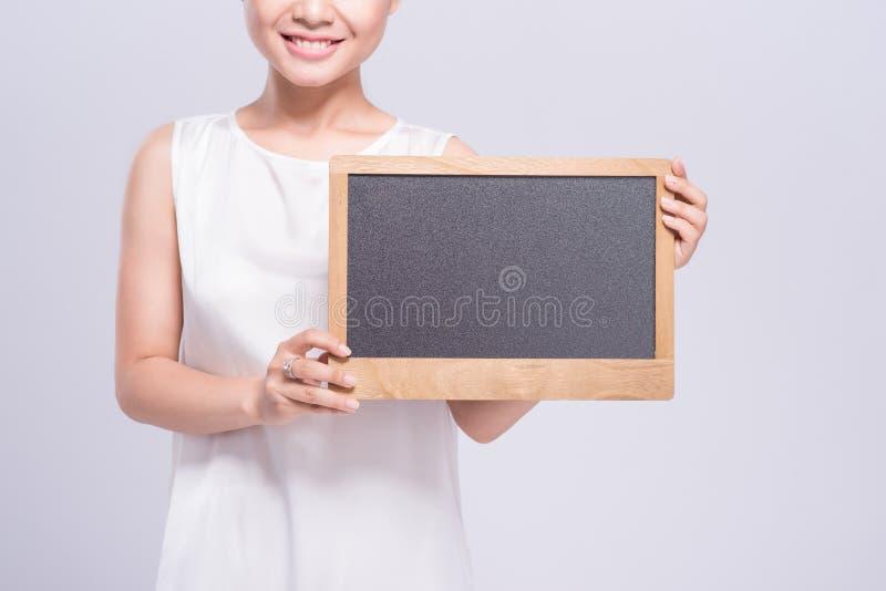 Vrolijke jonge vrouw in het witte teken van de hemdsholding over grijze bac stock foto's
