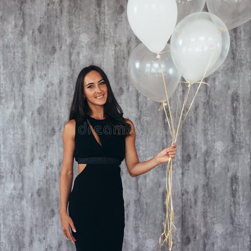 Vrolijke jonge vrouw met en ballons die bevinden zich glimlachen royalty-vrije stock foto's