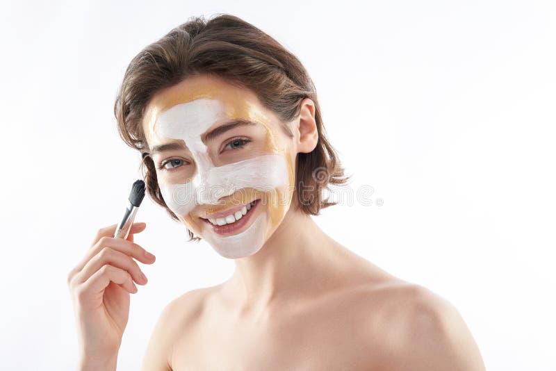 Vrolijke jonge vrouw met gezichtsmasker en borstel stock foto's