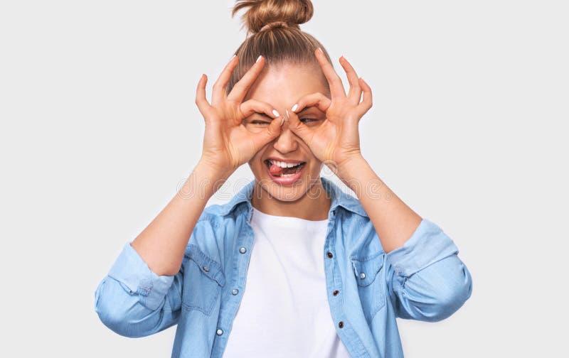 Vrolijke jonge vrouw met het kapsel van het blondebroodje, die O.k. gebaren met beide handen tonen, die binoculaire bril beweren  royalty-vrije stock foto's