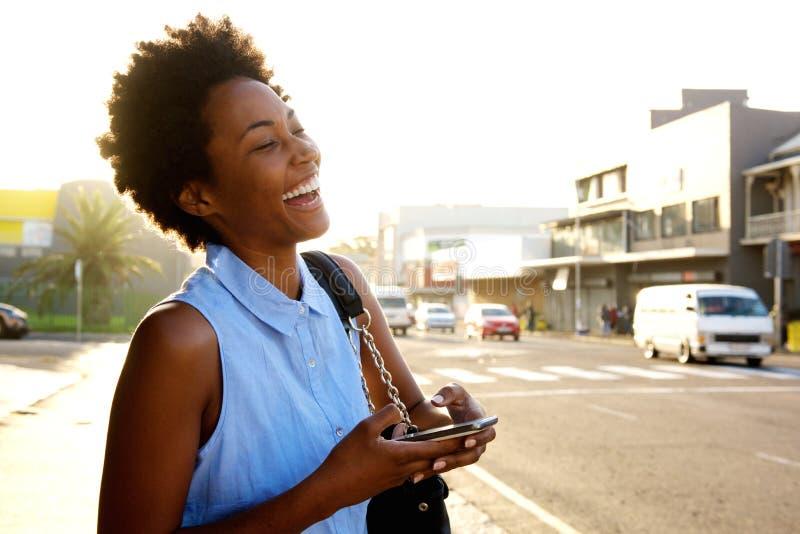 Vrolijke jonge vrouw met mobiele telefoon op de stadsstraat stock fotografie
