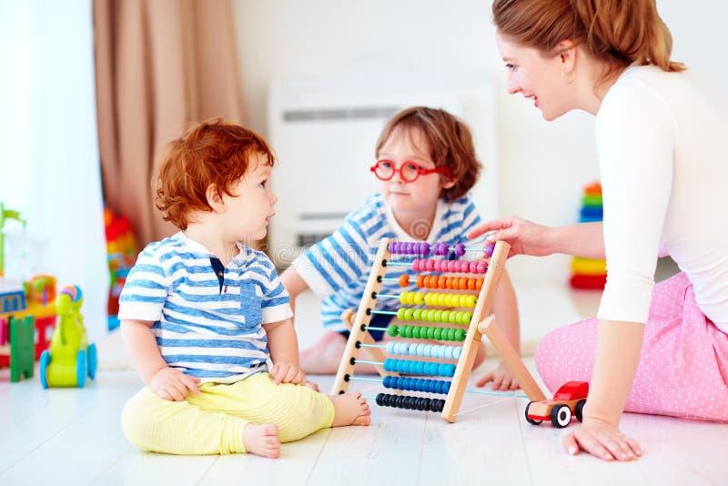 Vrolijke jonge vrouw, moeder speelspelen met jonge geitjes bij kinderdagverblijfruimte stock foto's