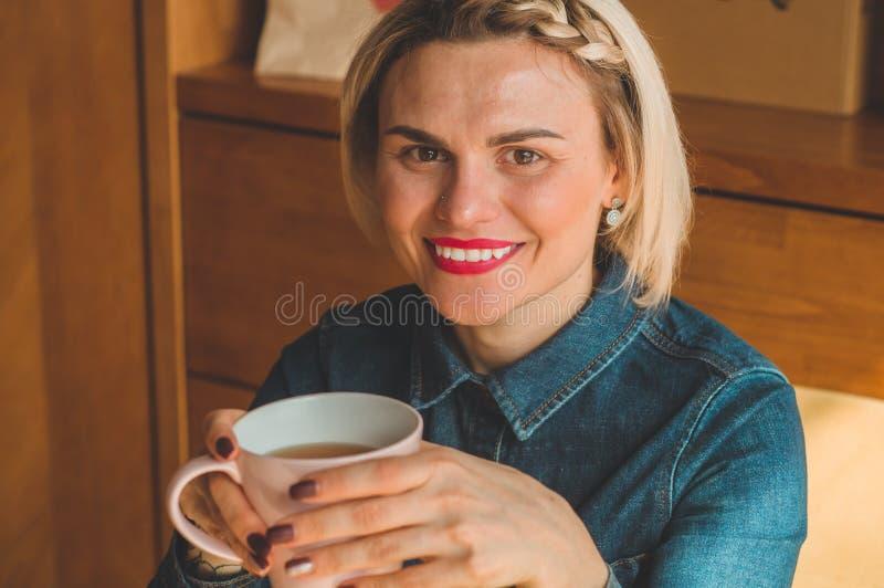 Vrolijke jonge vrouw warme koffie drinken of thee die van het genieten terwijl het zitten in koffie royalty-vrije stock foto