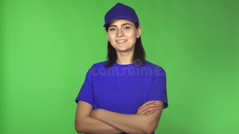 Vrolijke jonge vrouwelijke leveringsarbeider die aan de camera glimlachen stock afbeeldingen