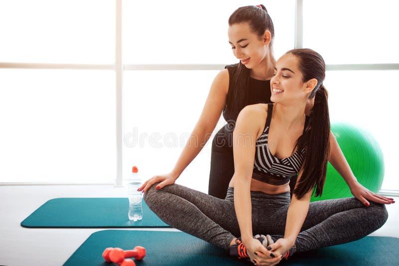 Vrolijke jonge vrouwen die samen lachen Zij kijken aan linkerzijde Aziatische modelhulp haar benen van de vriendenrek Zij zitten  royalty-vrije stock foto