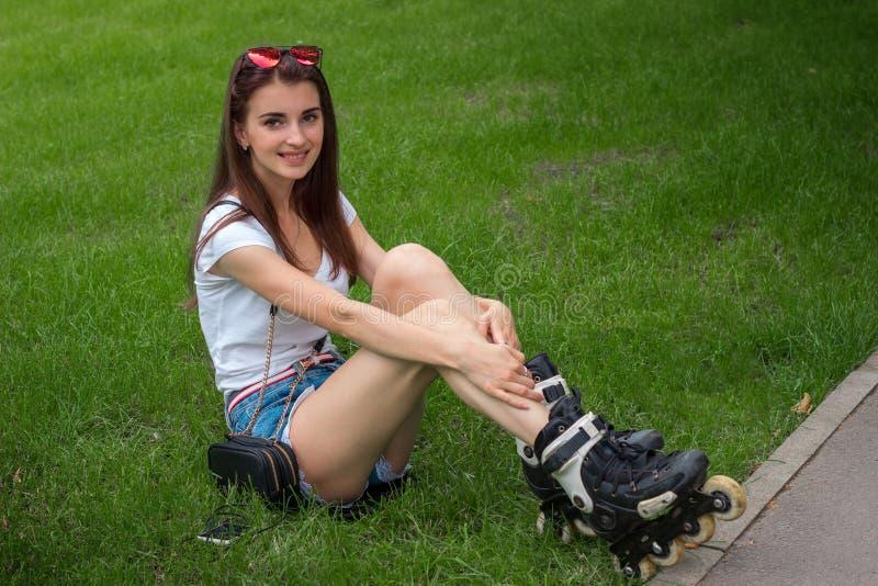 Vrolijke jonge vrouwenglimlachen op camera met rol op haar benen stock afbeelding