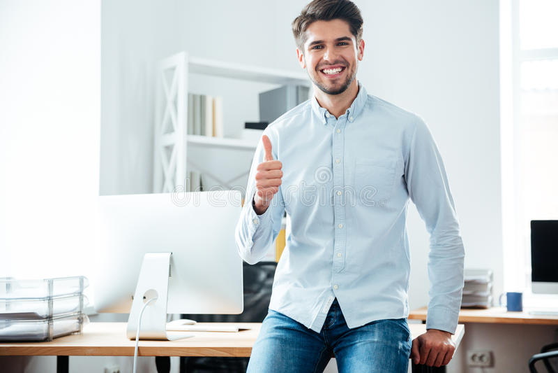 Vrolijke jonge zakenman die duimen in bureau tonen stock afbeeldingen