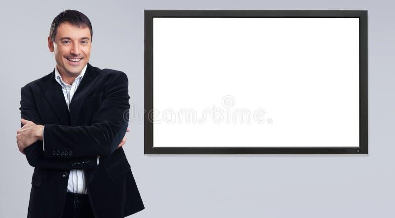 Vrolijke jonge zakenman die lege PC-monitor tonen royalty-vrije stock afbeelding