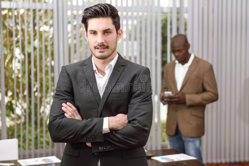 Vrolijke jonge zakenman in formalwear houdende gekruiste wapens stock afbeelding