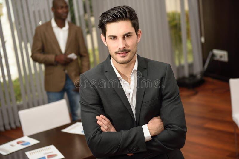 Vrolijke jonge zakenman in formalwear houdende gekruiste wapens stock foto's
