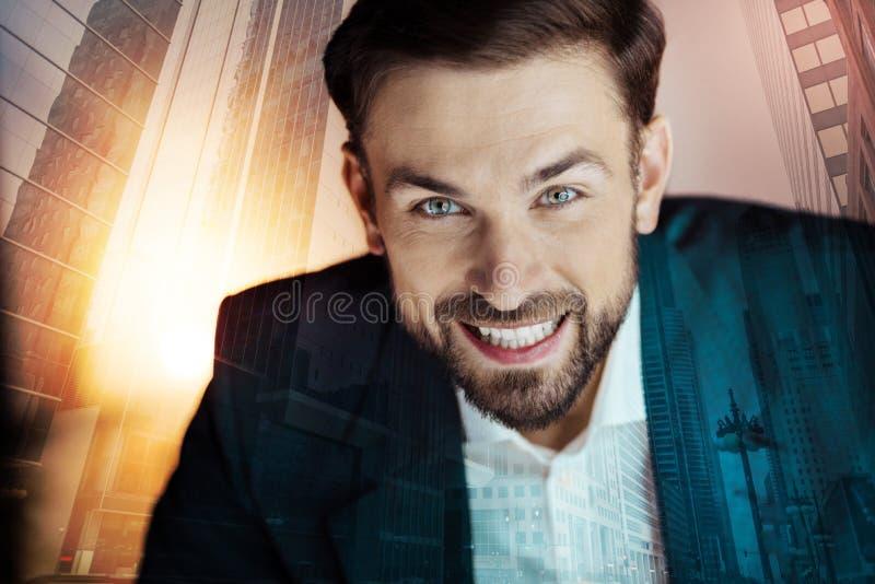 Vrolijke jonge zakenman in kostuum het glimlachen stock fotografie