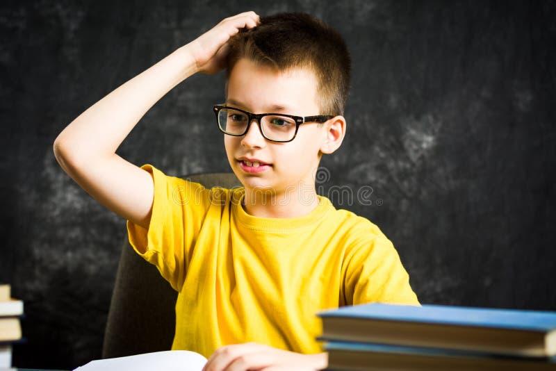 Vrolijke jongen die met bos van boeken over school denken royalty-vrije stock foto's