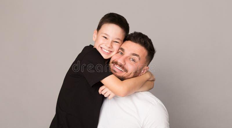 Vrolijke jongen die met zijn vader, gelukkig familieportret koesteren royalty-vrije stock afbeelding