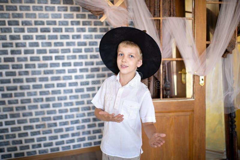 Vrolijke jongen die nieuwe tovenaarshoed dragen stock foto