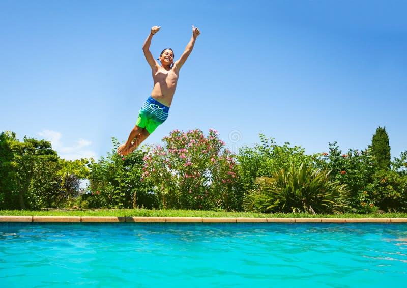 Vrolijke jongen die in openlucht zwembad springen royalty-vrije stock foto