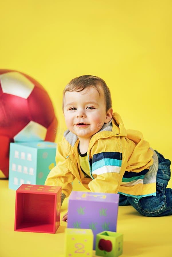 Vrolijke jongen het spelen stuk speelgoed bakstenen stock foto